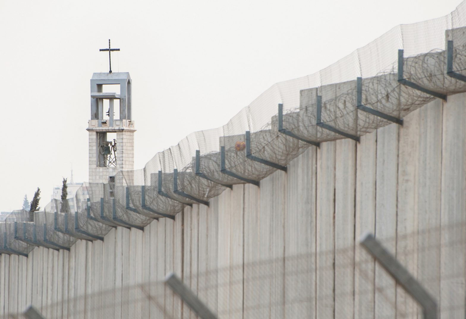 Image: The steeple of a Franciscan convent in the Aida refugee camp, near the Israeli separation wall in the West Bank. Photo: Ryan Rodrick Beiler
